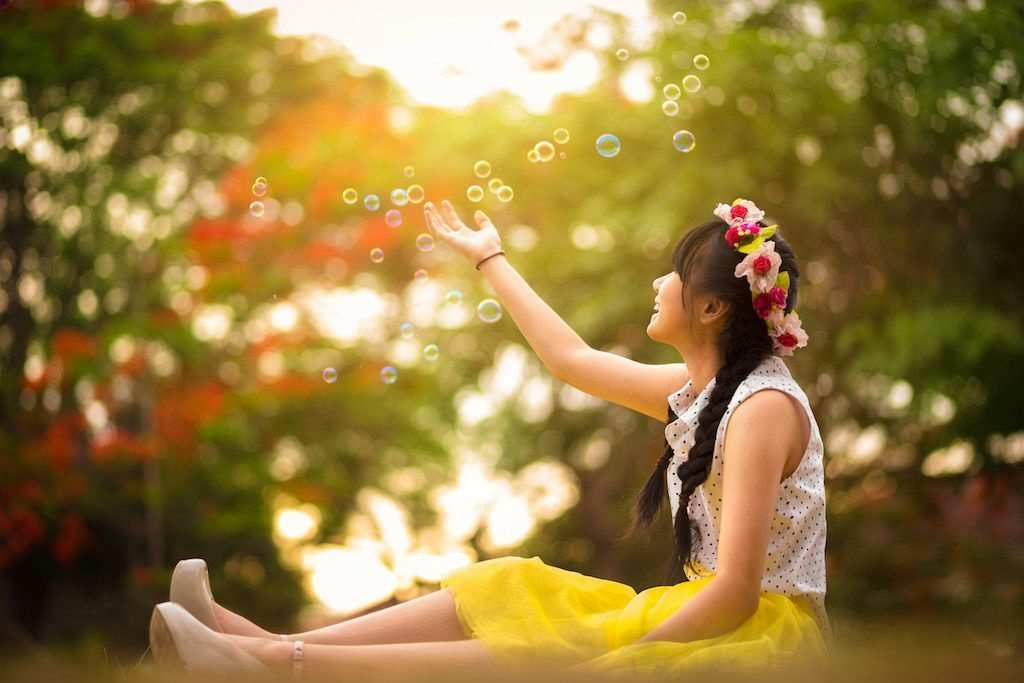 Asian teenager girl in the park under soap bubble rain