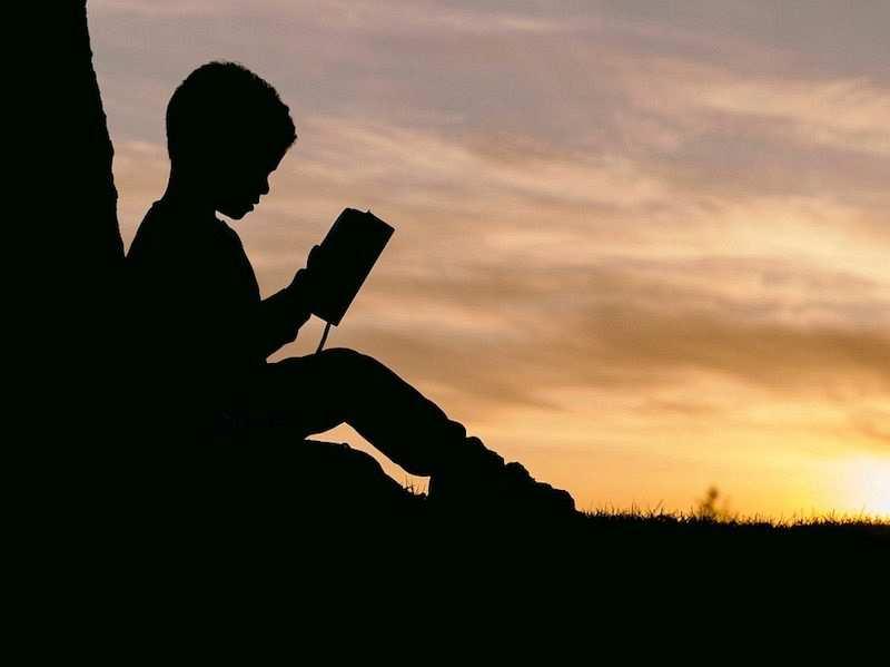 günbatımında kitap okuyan erkek çocuk